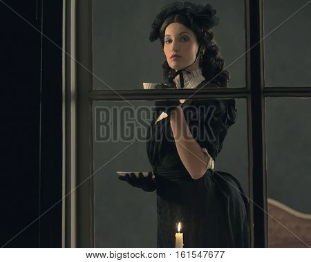 Vintage Victorian Girl Drinking Cup Of Tea Behind Window.