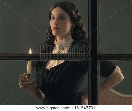 Retro Victorian Woman Holding Candlestick Looking Out Rainy Window.