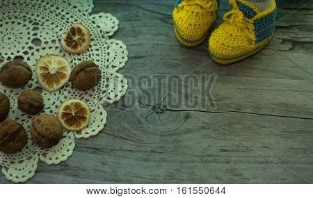 walnuts and knitted yelow sneakers on the desk