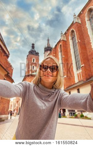 Female tourist stands on a background of the church of St. Mary in Krakow. Basilica Mariacka. Krakow. Poland.