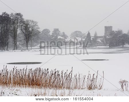 Winter scene withsettled and falling snow by Melbourne Pool Melbourne Derbyshire England looking towards the parish church