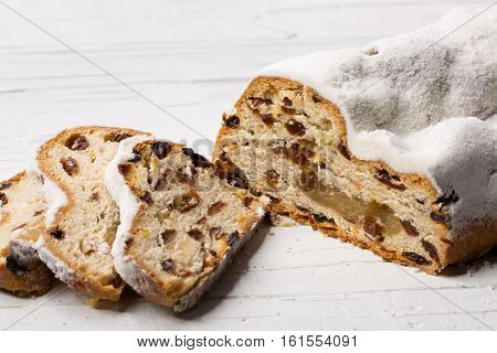 Christmas stollen partly in slices on white wooden background