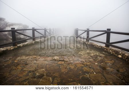 Wooden walkway lost in the fog. Torcal De Antequera Malaga Spain