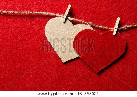 Valentine's day. Two hearts from felt and cardboard on rope with clothespin on red background