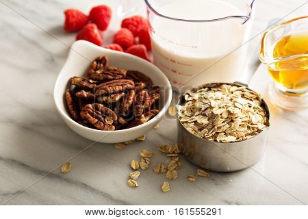 Cooking oatmeal with oats in a measuring cup, nuts and milk