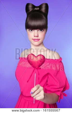 Attractive Teen Girl With Bow Hair Style, Brunette Young Model Holding Red Heart Isolated In Blue Ba