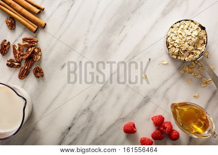 Cooking oatmeal with oats in a measuring cup, nuts and milk overhead shot with copyspace