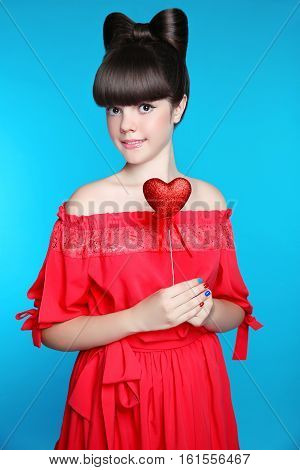 Smiling Teen Girl With Bow Hair Style, Brunette Young Model Holding Red Heart Isolated In Blue Backg