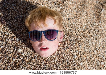 Boy In Sunglasses Partly Buried With Pebbles On Beach