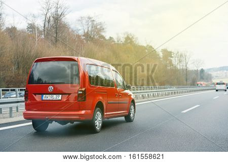 GERMANY - MARCH 26 2016: Point of view of a driver looking at a fast Volkswagen red mini van on highway autobahn on a spring day
