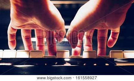 Scene of pianist hands from underneath angle playing piano Photo in vintage colors style.
