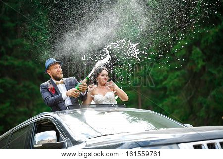 just married couple Bourne uncork champagne in hatch car