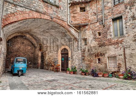 TODI, ITALY - SEPTEMBER 10: a picturesque old alley with dwellings and an ancient italian vehicle Ape Piaggio, on September 10, 2013 in Todi, Umbria, Italy