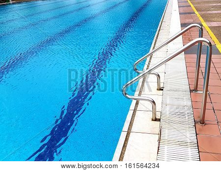 Side vew of bright blue swimming pool with sparking crystal clear water with ripples and horizontal lines and stainless steel handrail.