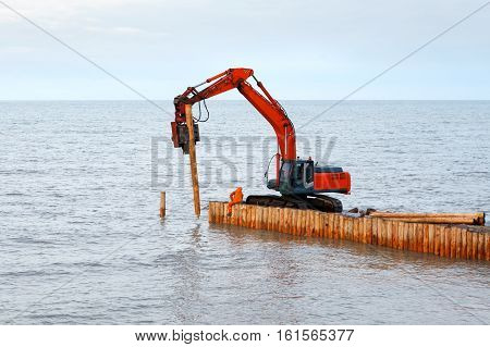 palification piles of larch. Construction of wooden breakwaters at sea