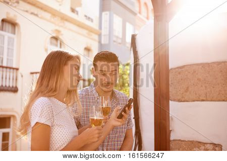 Couple Looking At Cellphone With Surprise