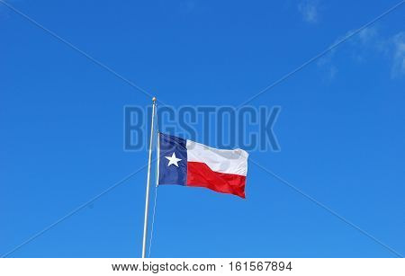 Texas flag flying high in the clear blue sky.