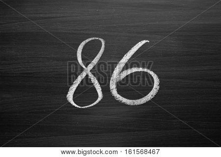 number eighty six enumeration written with a chalk on the blackboard