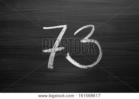 number seventy three enumeration written with a chalk on the blackboard