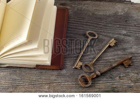 antique book and old keys over rustic wooden background. grunge vintage backdrop