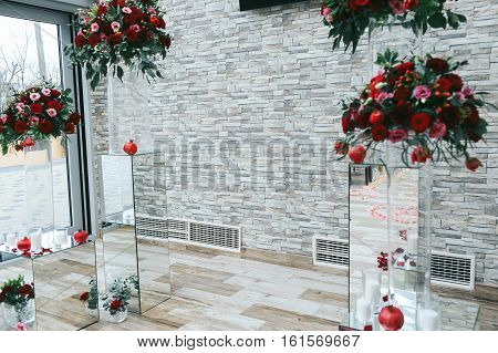 White Brick Wall Decorated With Red Bouquets And Glass Boxes In The Front Side