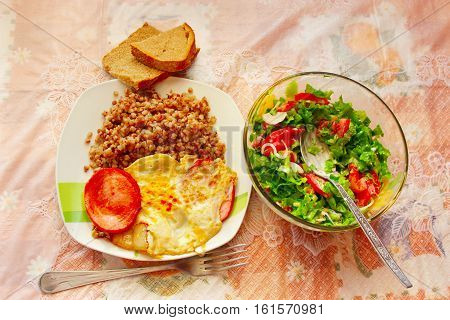 dish from boiled buckwheat boiled sausage fried scrambled eggs and fresh vegetables pieces of tomatoes and lettuce