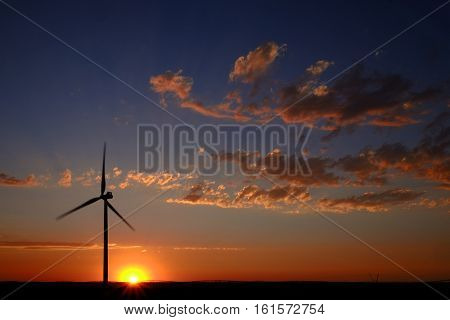 Windmill with sunset and clouds generating electricity and sustainable power