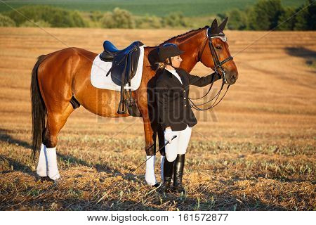 Happy Woman with her Horse - Beautiful young horsewoman next to her horse. equestrian.