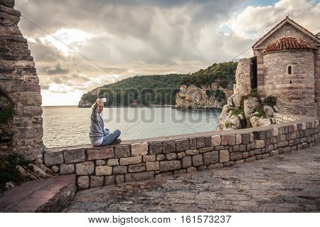 Woman traveler taking selfie photo during sunset sitting on stone wall with sea and dramatic sky on background in old Europe town during traveling