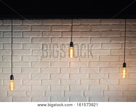 Old lighting electric bulb Retro lamp on a background of a white brick wall. Edison bulb hanging on a wire. Three bulbs on a wire with blank place