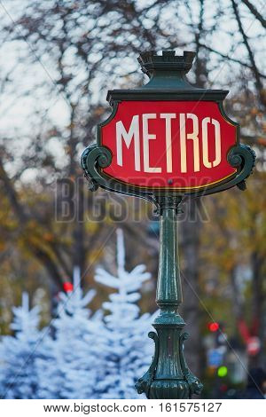 Sign Of Parisian Underground With Christmas Trees Covered With Snow