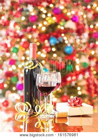 Wine glasses vintage cork screw present and unopen wine bottle on Mahoney table with bright Christmas tree lights in background. Vertical format layout.