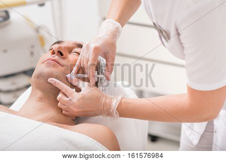 Close-up of surgeon arms making hyaluronic acid injection into male face. Man is lying with relaxation