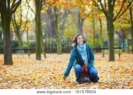 Cheerful young Parisian girl walking in park on a sunny fall day and having fun