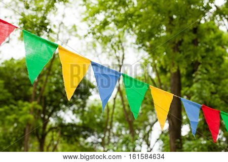 Color triangular flags with white dots on the nature background