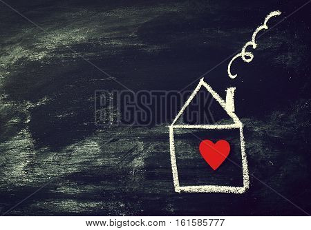 Home or Love Concept. Painted House with Red Heart on a Black Chalkboard. Top View with Copy Space.