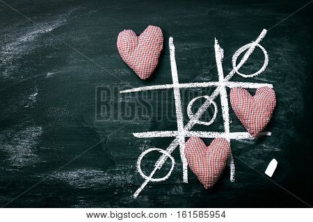 Tic Tac Toe Game. Love or Valentine's Day Concept with Chalkboard and Hearts on a Old Dark Background. Top view with copy space.