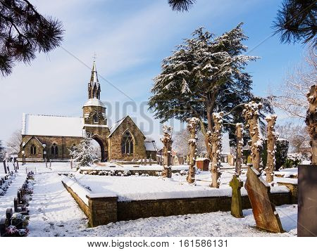 Peaceful snowy winter scene at the cemetery in Melbourne Derbyshire England.