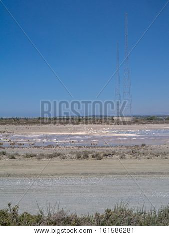 Lady's Mile Limassol Cyprus of the salt lake with a few pylons and blue sky.