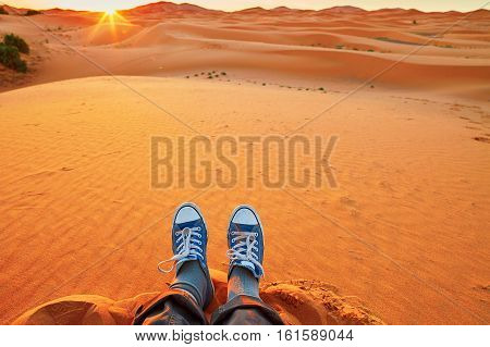 Woman Relaxing On Sand Dunes And Looking At Sunrise In Sahara Desert