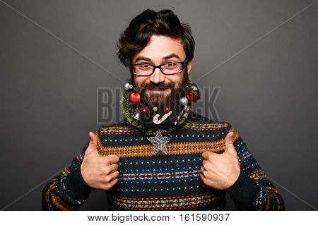 young man showing LIKE gesture. Christmas festive guy in sweater ready for winter holidays