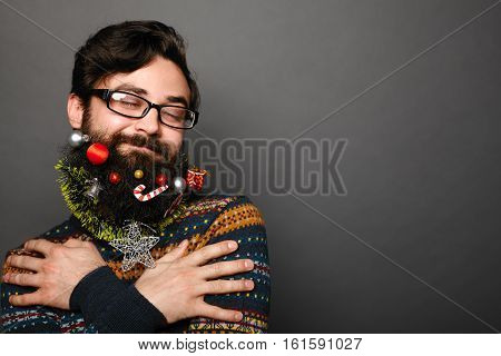Young man with decorated christmas beard making a wish with eyes closed over grey background with copy space