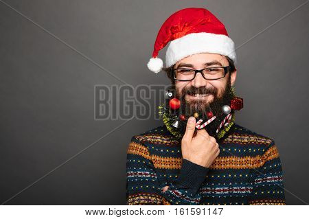bearded man with mustache and decorated beard as christmas tree on grey wall background with copy space.