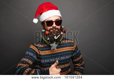 caucasian man with big beard in christmas sweater showing Like gesture. Bearded male shows thumbs up over grey background