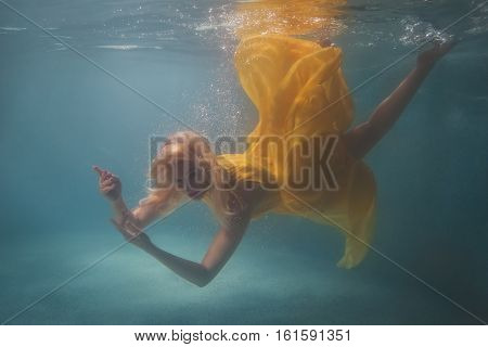 Woman in yellow dress swimming underwater in the pool.