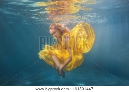 Woman in yellow dress dancing underwater showing figures.