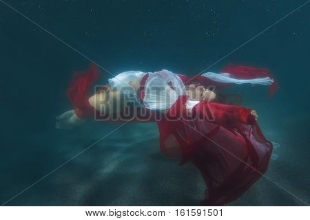 Woman in red dress dancing underwater in the pool.