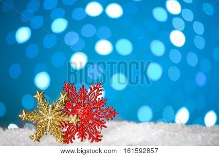 Christmas background with a decorative snowflakes on snow, blue bokeh