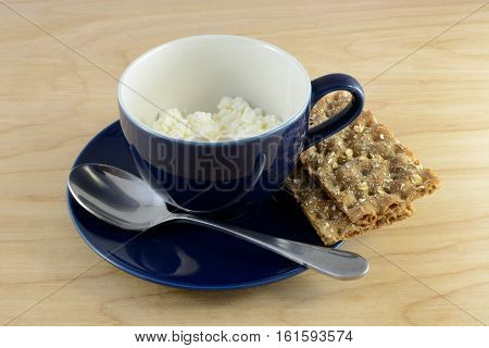 Cottage cheese in blue cup and crispbread crackers on saucer with spoon