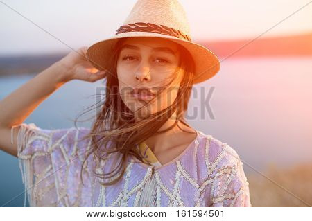 Close up face of beautiful latin trendy woman wearing a stylish hat with lens flare